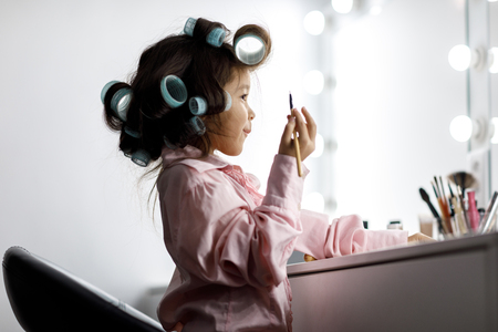 Cute little girl playing with her mothers cosmetic Stockfoto