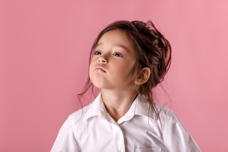 Cute proud little girl in white shirt with hairstyle looking to camera on pink background. I am the best. Human emotions