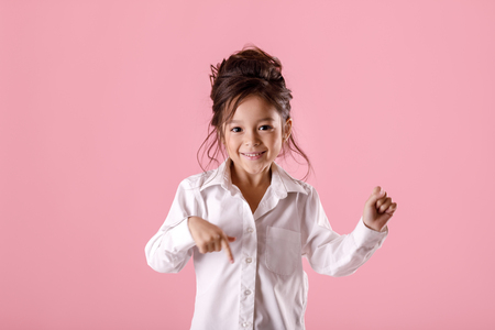 Cute smiling little girl in white shirt pointing down and looking to camera on pink background. Human emotions and facial expression Фото со стока