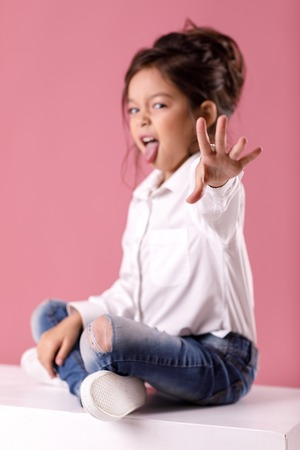 Cute little child girl in white shirt with hairstyle showing tongue on pink background. Human emotions and facial expression