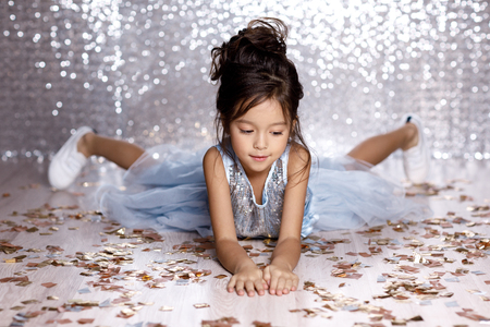 little child girl in blue dress sitting on the floor with confetti on background with silver bokeh. birtday party