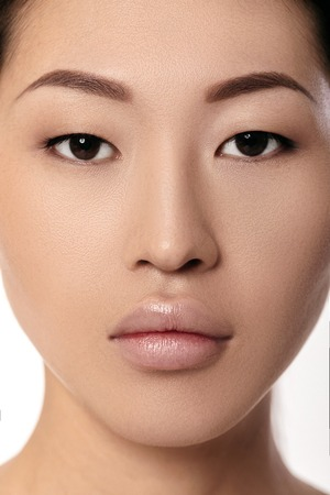 close-up portrait of beautiful young asian woman on white background closeup. girl with clean skin. Female lips after augmentation procedure Imagens