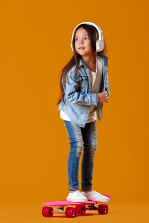 Stylish little child girl in headphones with skateboard in jeans clothes on orange background