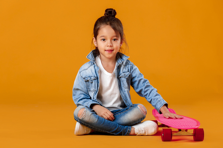 Stylish little child girl with skateboard in jeans clothes on orange background Фото со стока - 117401948