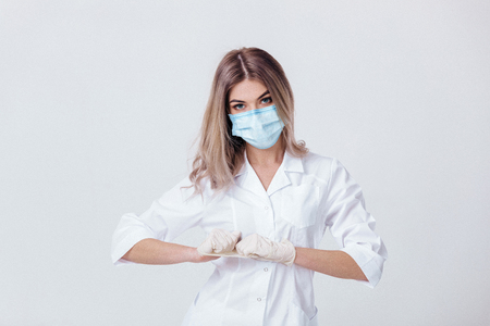 Portrait of woman doctor with face mask wearing white medical gloves Stockfoto