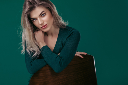 fashion portrait of sensual beautiful blonde woman in green dress sitting on chair and looking at camera against green background Banque d'images