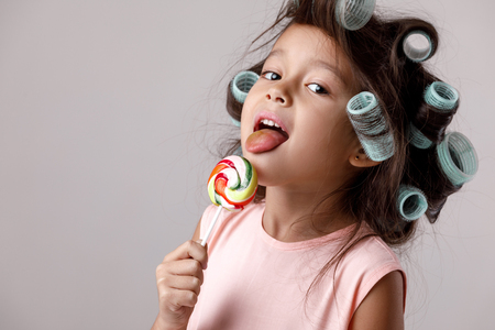 Funny little child girl in pink dress and hair curlers eating lollipop on gray background. Stockfoto