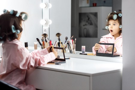 Cute little girl playing with her mothers cosmetic in front of the mirror at home Фото со стока