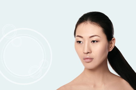 Spa portrait of attractive asian woman with arrows on her face on white background. Face lifting concept. Plastic surgery treatment, medicine Imagens