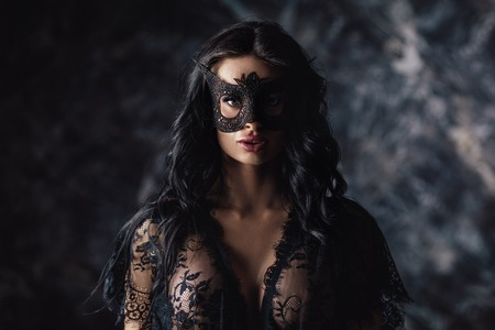 portrait of beautiful woman in lace black lingerie and carnival mask on dark background