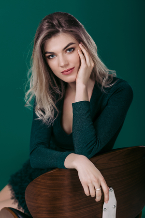 Sensual beautiful blonde woman in green dress sitting on chair and looking at camera against green background