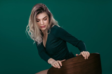 fashion portrait of beautiful blonde woman in green dress sitting on chair against green background. space for text