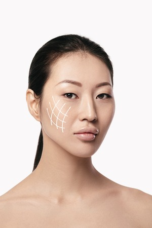 Spa portrait of attractive asian woman with arrows on her face on white background. Face lifting concept. Plastic surgery treatment, medicine Stock Photo