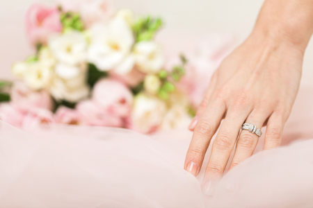 brides hand with a wedding ring with diamonds on the background of a bouquet of flowers