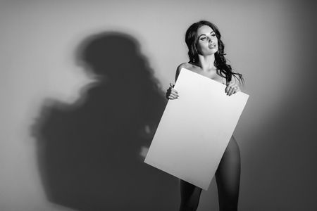 Sexy naked brunette woman holding empty board. attractive girl with blank board with copy space. black and white