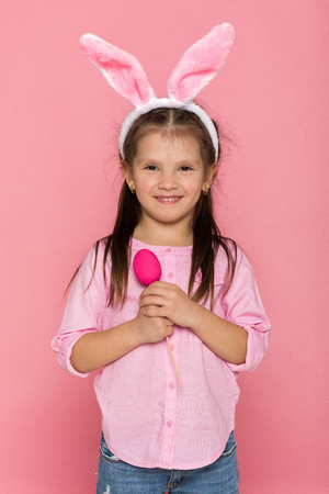 Portrait of cute little child girl with Easter bunny ears holding colorful eggs on pink background. Happy easter Standard-Bild - 119974662