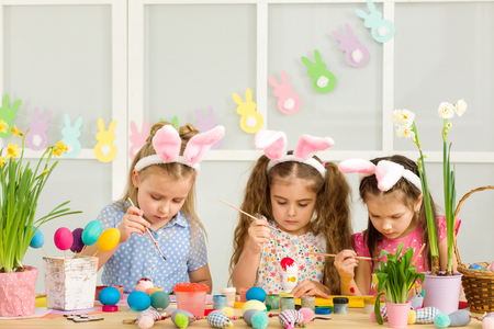 cute kids painting Easter eggs at home. adorable children prepare for easter Stock Photo - 119961773