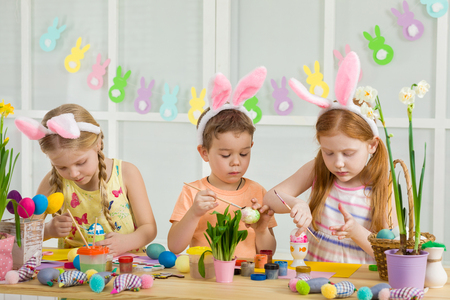 cute kids painting Easter eggs at home. adorable children prepare for easter Stock Photo - 120542384
