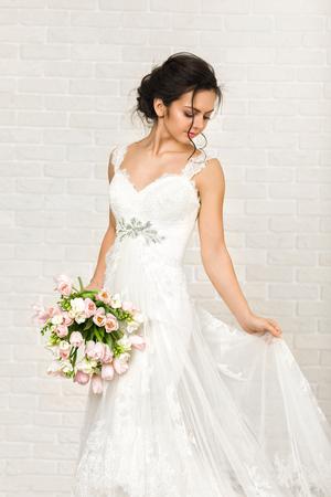 Porträt der schönen Braut mit Hochzeitsblumenstrauß aus rosa Tulpen