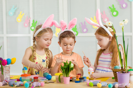 cute kids painting Easter eggs at home. adorable children prepare for easter Stock Photo - 120544305