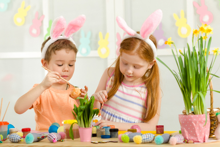 cute kids painting Easter eggs at home. adorable children prepare for easter