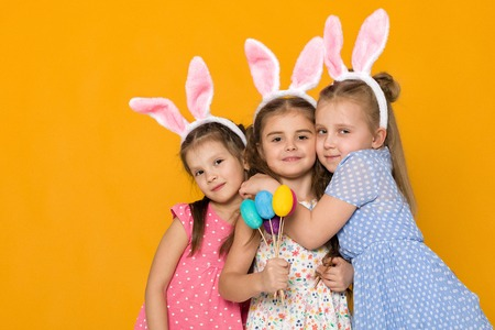 three little girls with Easter bunny ears holding colorful eggs on yellow background. Happy easter. cute children Stock Photo - 120792813