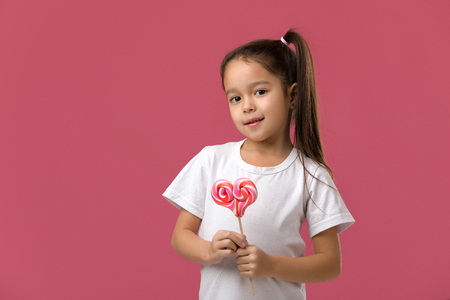 Beautiful cute little child girl with sweet candy lollipop isolated on pink background 스톡 콘텐츠