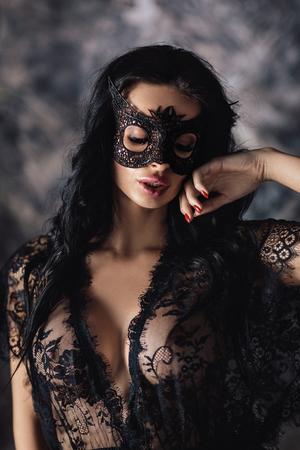 portret van mooie vrouw in kanten zwarte lingerie en carnavalsmasker op donkere achtergrond
