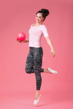 beautiful athletic smiling woman jumping with the ball on a pink background