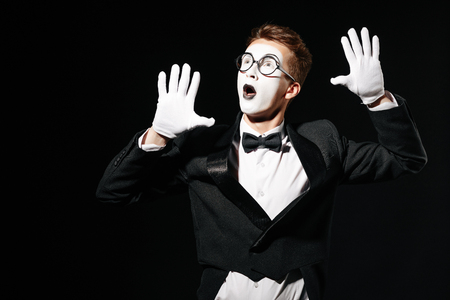 portrait of mime man holding his hands on an invisible wall on black background
