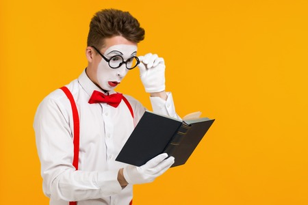 portrait of mime man artist reading book isolated on yellow background. copy space for text Foto de archivo