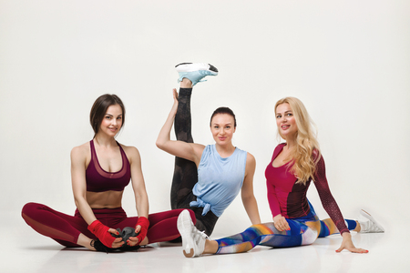 Group of fit female friends wearing sportswear posing together on white background. woman doing yoga or pilates exercise. Splits