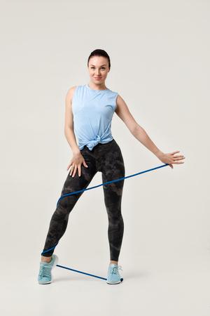 Beautiful sports woman holding skipping rope and looking at camera