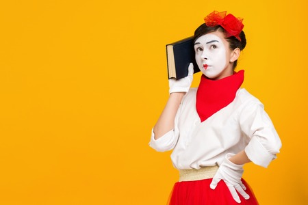 portrait of mime woman artist reading book isolated on yellow background . space for text