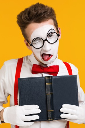 portrait of mime man artist with book ape isolated on yellow background