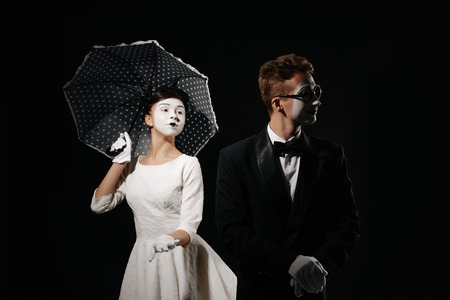 portrait of couple mime with umbrella on black background. man in tuxedo and glasses and woman in white dress. relationship