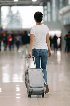 traveler young woman walking with suitcase in an airport