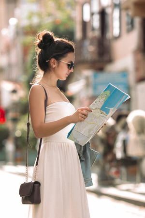 beautiful caucasian tourist woman looking at the map on the street of city Imagens