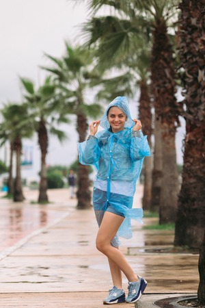 young woman tourist in raincoat smiling and looking at the camera under rain