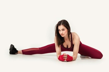 beautiful woman with red boxing tape on wrist stretching legs