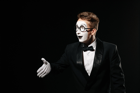 portrait of mime man in tuxedo and glasses giving hand for handshake on black background