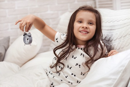 cute happy little child girl in pyjamas with clock in bed. good morning