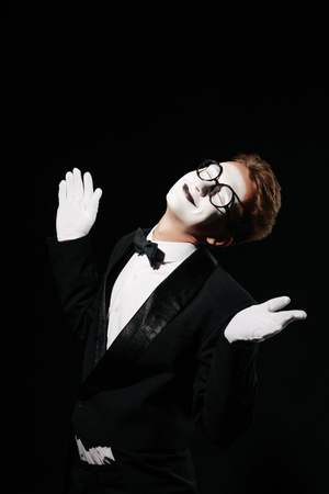 portrait of smiling mime man in tuxedo and glasses on black background Stockfoto