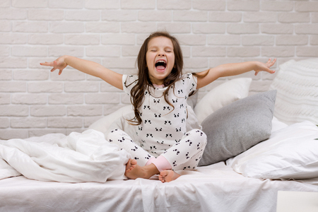 cute happy little child girl in pyjamas in bed. good morning