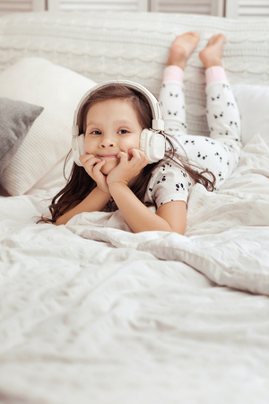little child girl listening to the music with the headphones on bed. happy morning