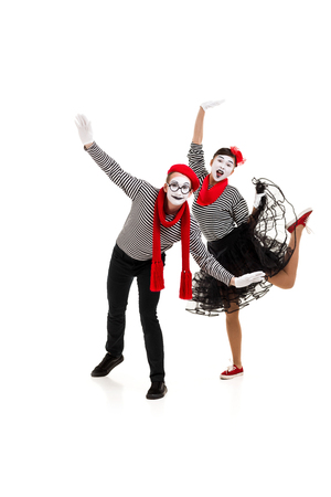 mimes in striped shirts. Male and female mimes dancing with wide open arms isolated on white background