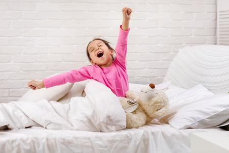 jolie petite fille se réveille du sommeil et bâille dans son lit le matin