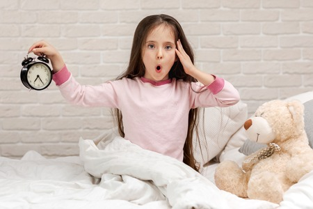 cute surprised little child girl in pyjamas with clock in bed. good morning Banco de Imagens