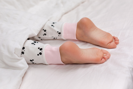 Pair of kid bare feet in bed on white sheets