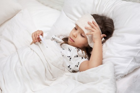 Sick little child girl lying in bed with thermometer. Cold flu season Stockfoto